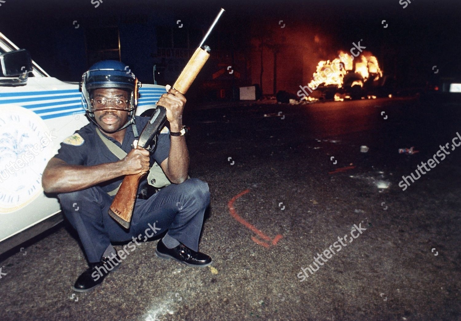 Miami Policeman Squats Behind Policecar Holding Rifle throughout Miami Super Bowl Riot